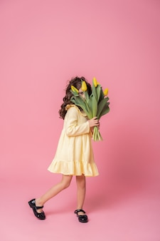 Smiling girl in yellow dress on pink studio background. cheerful happy child with tulips flower bouquet.