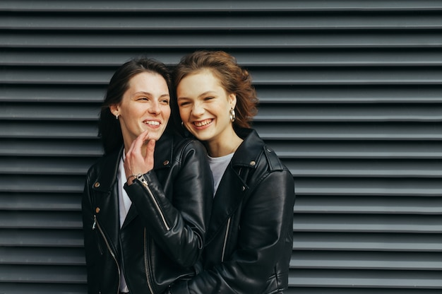 Smiling girlfriends in leather jackets