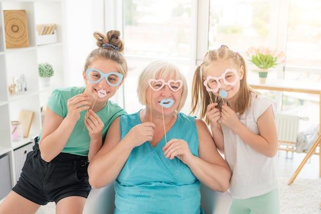 笑顔の女の子と年配の女性が明るい部屋で紙コップと唇で