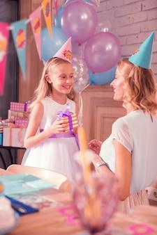笑顔の女の子。素敵なパーティハットをかぶってゲストを待っている陽気な女の子と彼女の母親の笑顔