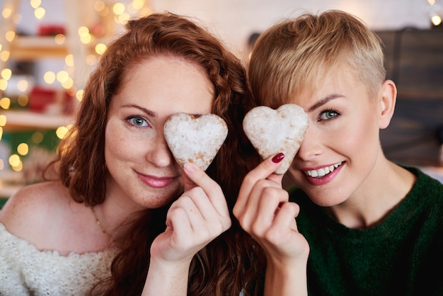 Smiling girls holding heart shaped gingerbread cookies