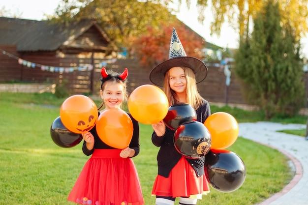 Улыбающиеся девушки в костюме хэллоуина, держа на открытом воздухе оранжевые и черные воздушные шары, весело проводят время, встречая хэллоуин.