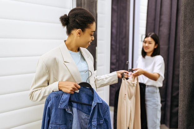 피팅 룸, 옷가게에서 웃는 소녀. 패션 부티크에서 쇼핑하는 여성, 쇼핑 중독자, 의류를 입어 보는 쇼핑객