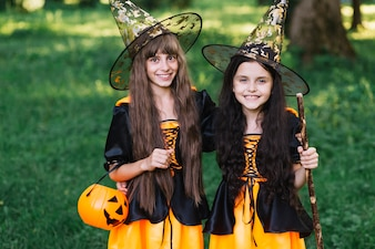 Smiling girls in sorceress costumes in park