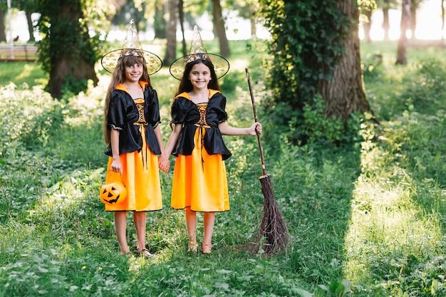 Улыбающиеся девушки в костюмах ведьмы в зеленом солнечном парке