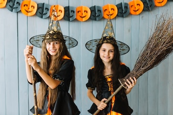 Smiling girls in witch suits holding broomstick and stick