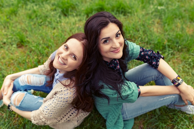 Smiling girls sitting back to back on grass