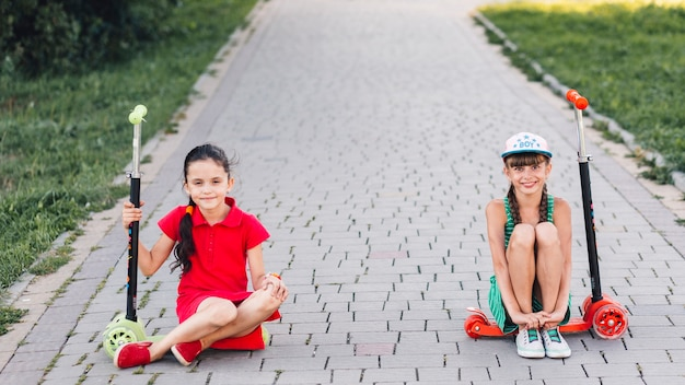 Smiling girls sitting on their push scooter