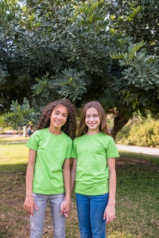 Smiling girls standing in front of tree in park
