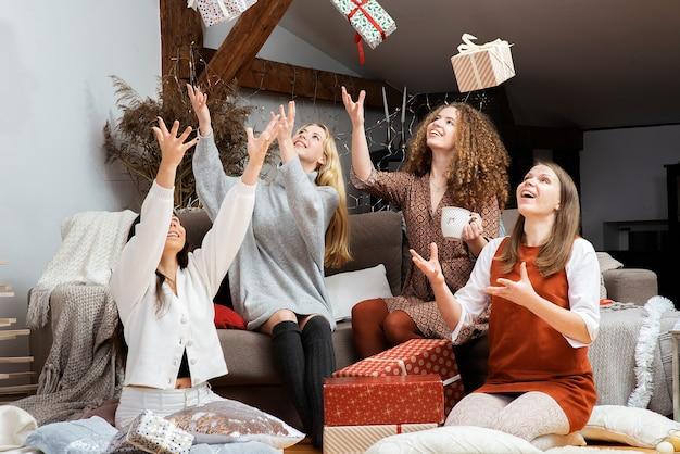 공중에 크리스마스 선물을 던지고 웃는 소녀 프리미엄 사진