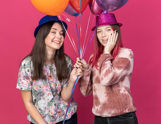 ピンクの壁に分離された風船を保持しているパーティー帽子をかぶって笑顔の女の子