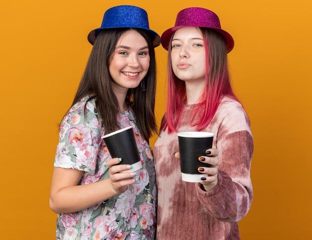 Улыбающиеся девушки в партийной шляпе, протягивая чашку кофе перед камерой