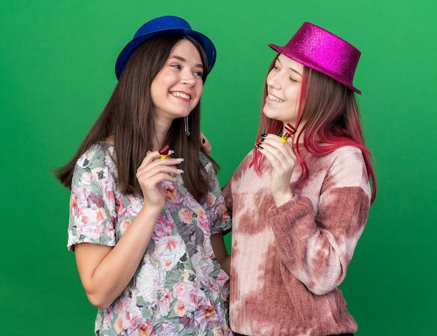 Smiling girls wearing party hat holding party whistle look at each other isolated on green wall