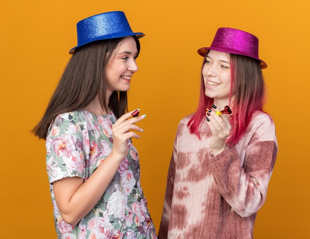 Smiling girls wearing party hat holding party whistle look at each other