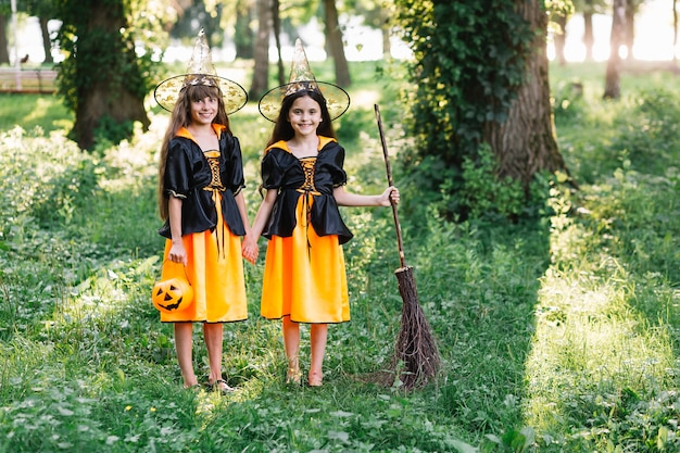 Smiling girls in witch costumes in green sunny park
