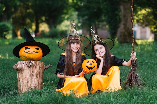 Smiling girls in witch costumes sitting on grass in park