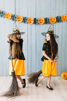 Smiling girls in witch suits holding broomsticks