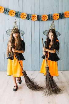 Smiling girls in witch suits posing with broomsticks