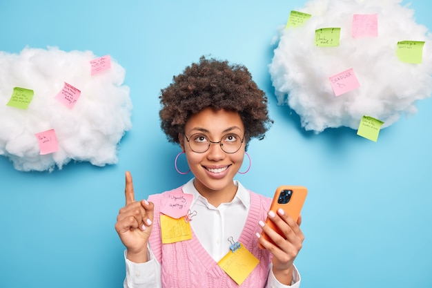 Smiling glad afro american female office worker points upwards gives recommendations how to scheme or plan working day writes ideas and tasks to do on colorful stickers uses modern smartphone