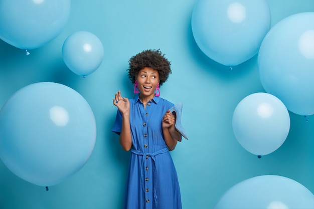 Smiling glad afro american woman chooses outfit for birthday party, holds blue shoes on high heels to fit dress, looks aside happily, poses near inflated balloons flying around. women, clothes