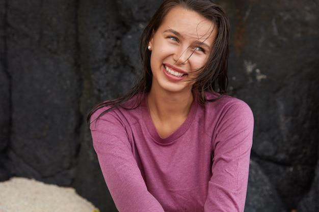 La donna caucasica felice sorridente guarda felicemente da parte