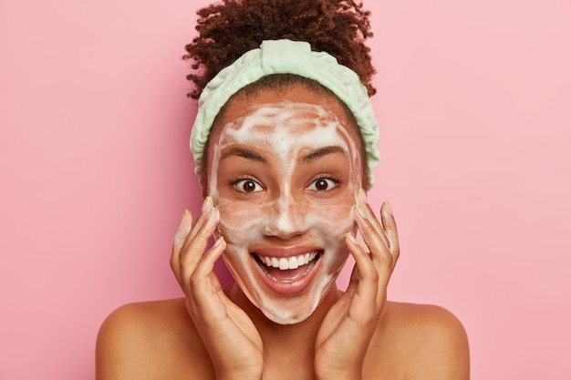 Smiling glad dark skinned young woman puts soap on face for cleansing, washes with cold water, wants to have healthy fresh skin., wears headband, looks positively, stands naked indoor