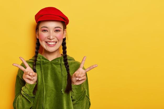 기쁜 예쁜 아시아 십 대 소녀 미소는 두 손으로 평화 제스처를 보여주고 광범위하게 미소