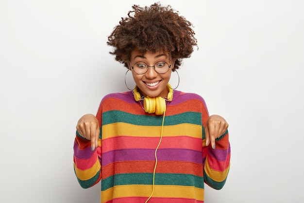 Smiling glad woman points down, proposes cool offer, looks happily at floor, wears transparent eyewear and striped jumper