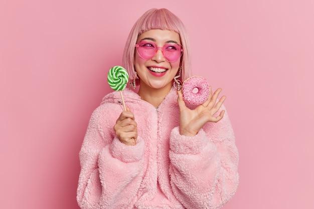 웃는 매력적인 아시아 십 대 소녀는 기꺼이 옆으로 막대기에 막대 사탕과 식욕을 돋우는 도넛을 보유하고 보인다