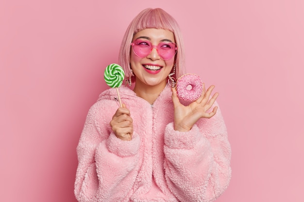 Smiling glamour asian teenage girl looks gladfully aside holds lollipop on stick and appetizing doughnut