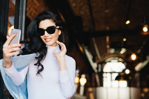 Smiling glamour woman in sunglasses, white blouse and jacket posing into camera of her smartphone
