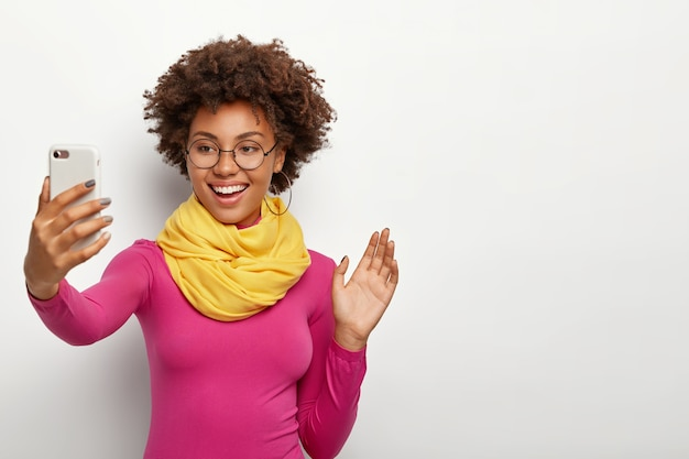Smiling good looking afro girl with crisp hair, waves palm in camera of smartphone, makes video call