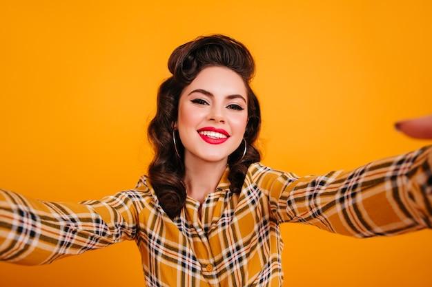 Улыбается красивая женщина, делающая селфи на желтом фоне. блаженная девушка кинозвезды позирует в клетчатой рубашке.