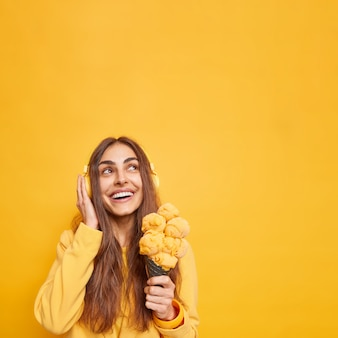 Sorridente bella donna con espressione allegra focalizzata sopra tiene volentieri un gustoso cono gelato pensa a qualcosa di piacevole mentre ascolta musica tramite le cuffie posa contro il muro giallo