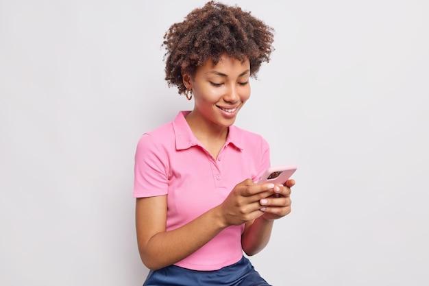 곱슬머리를 하고 웃고 있는 잘 생긴 여성은 흰색 벽에 격리된 캐주얼한 분홍색 티셔츠를 입고 문자 메시지를 보내고 뉴스 피드를 스크롤하기 위해 휴대폰을 사용합니다.