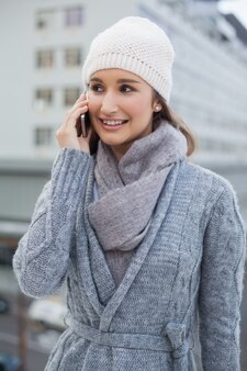 Smiling gorgeous woman wearing winter clothes having a call