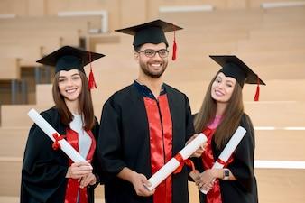 Smiling graduates keeping diplomas.
