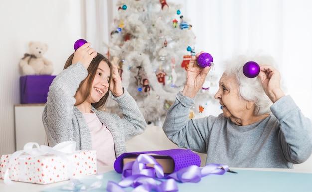 クリスマスに装飾的なボールで遊んでいるおばあちゃんの笑顔の孫娘