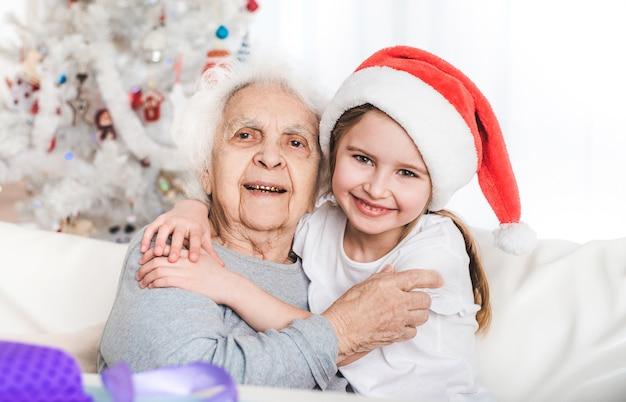 クリスマスにおばあちゃんと抱き締めるサンタの帽子の孫娘の笑顔