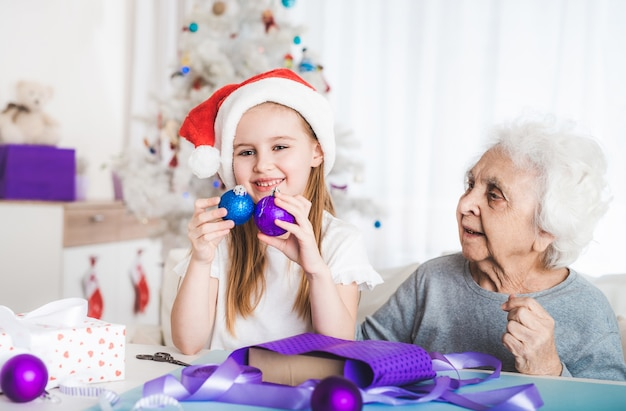 サンタの帽子をかぶった笑顔の孫娘は、クリスマスに装飾的なボールを保持しているおばあちゃんと一緒に座る