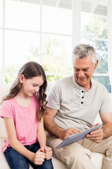 Smiling grandfather and granddaughter using tablet on the sofa