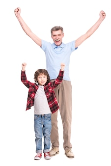 Smiling grandfather and his cute grandson raised arms up.
