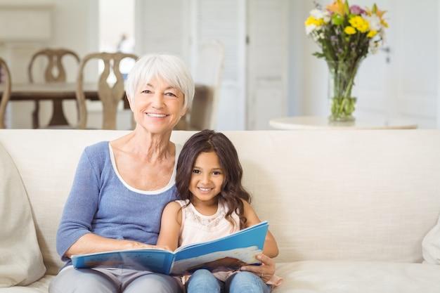 祖母と孫娘の写真アルバムが付いているソファーに一緒に座っている笑顔