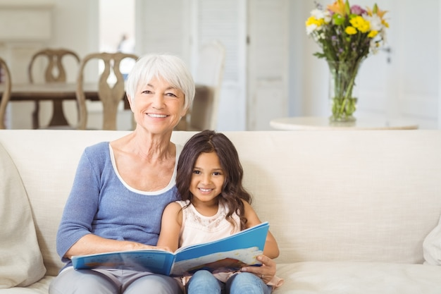 Smiling grandmother and granddaughter sitting together on sofa with photo album