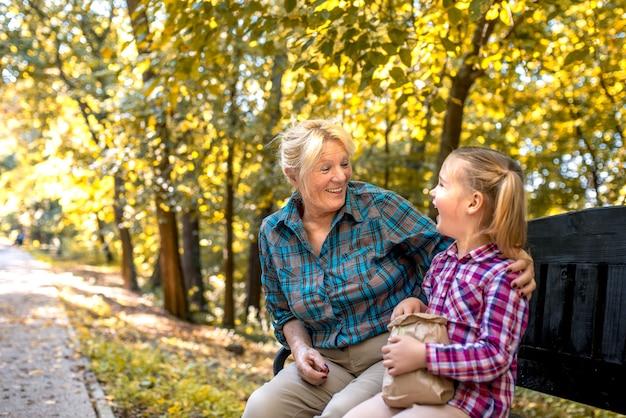 공원에서 그녀의 여성 손자를 포옹 웃는 할머니