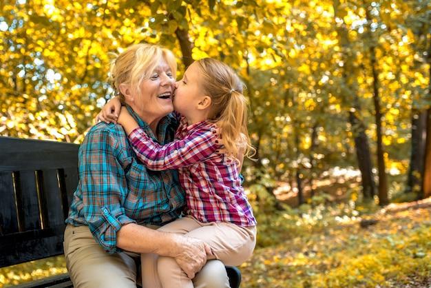 Nonna sorridente che abbraccia il suo nipote femminile nel parco