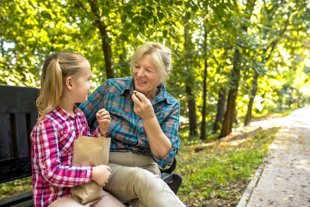 公園で彼女の女性の孫と一緒にベンチに座っている笑顔の祖母
