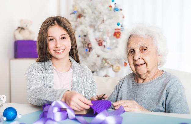 クリスマスに贈り物を飾る孫娘と祖母の笑顔