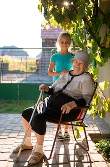 Smiling grandmother with granddaughter in the yard