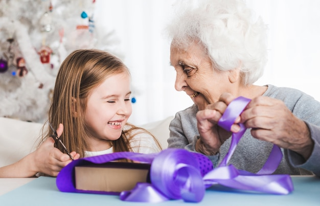 クリスマスに一緒に贈り物を飾る小さな孫娘と一緒に笑顔の祖母